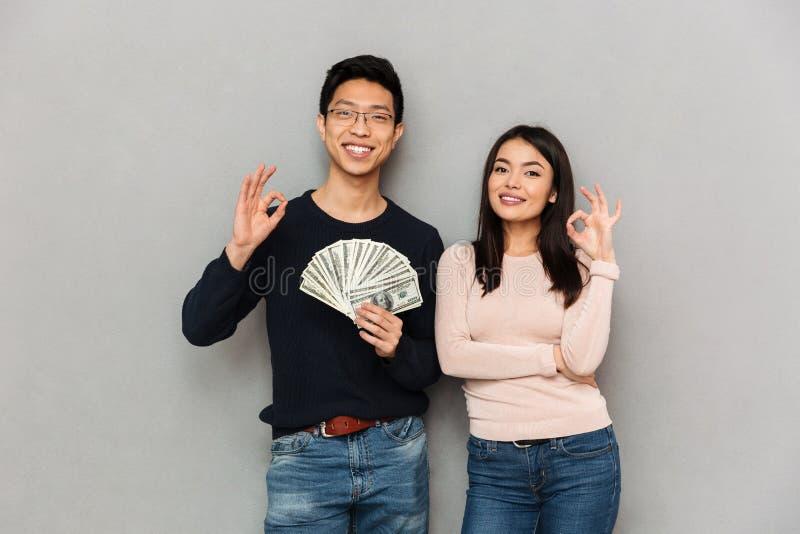 Aufgeregte junge asiatische liebevolle Paare, die das Geld zeigt okaygeste halten lizenzfreie stockbilder