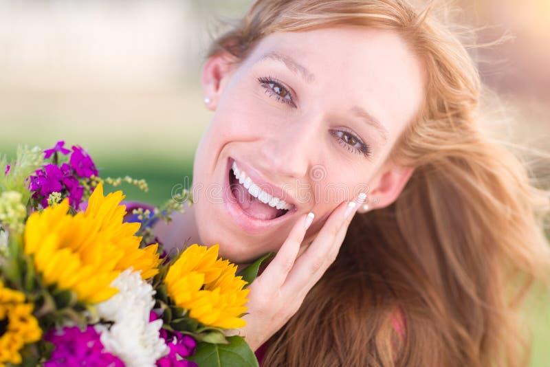Aufgeregte junge erwachsene Brown gemusterte Frau, die Blumenstrauß von Blumen hält stockbild