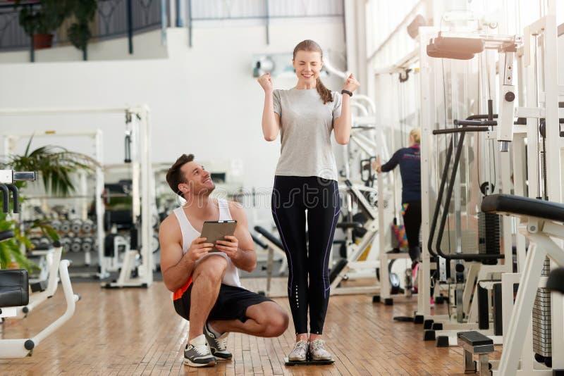 Aufgeregte junge Frau auf Gewichtsskala an der Turnhalle lizenzfreie stockbilder