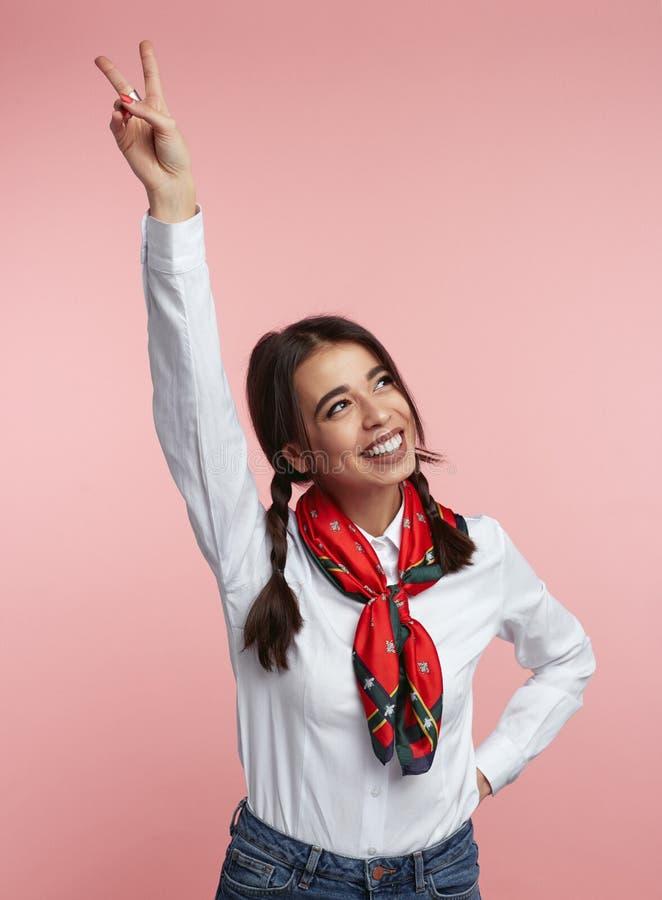 Aufgeregte junge Frau in der zufälligen Ausstattung lächelnd und Friedensgeste mit der angehobenen Hand bei der Stellung zeigen lizenzfreie stockfotografie