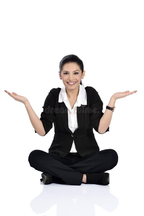 Aufgeregte junge Frau, die auf dem Boden sitzt lizenzfreie stockbilder