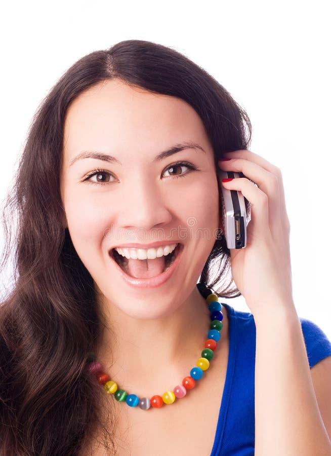 Aufgeregte junge Frau, die auf dem Cell-phone spricht stockfoto