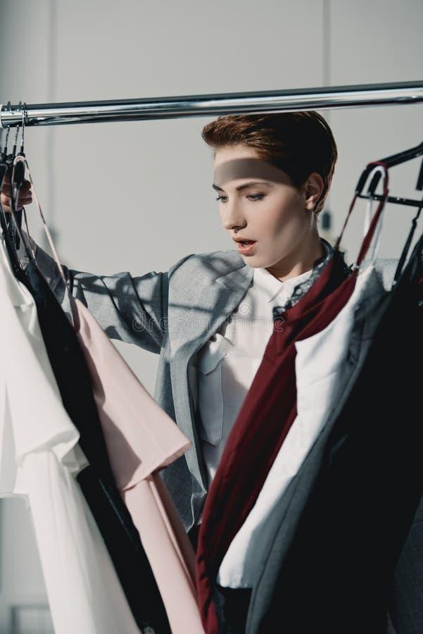 aufgeregte junge Frau, die Kleidung wählt stockfotos