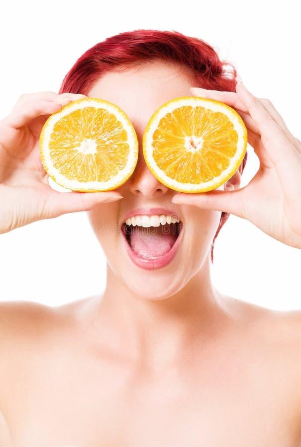Aufgeregte junge Frau, die Orangen über ihren Augen hält lizenzfreie stockfotografie