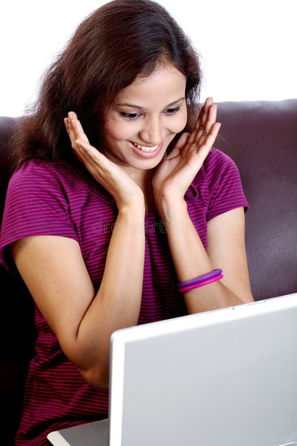 Aufgeregte junge Frau mit Laptop auf Sofa lizenzfreie stockbilder