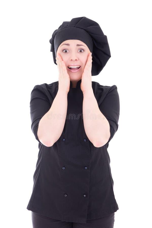 Aufgeregte Junge kochen Frau in der schwarzen Uniform, die auf Weiß lokalisiert wird stockfotos