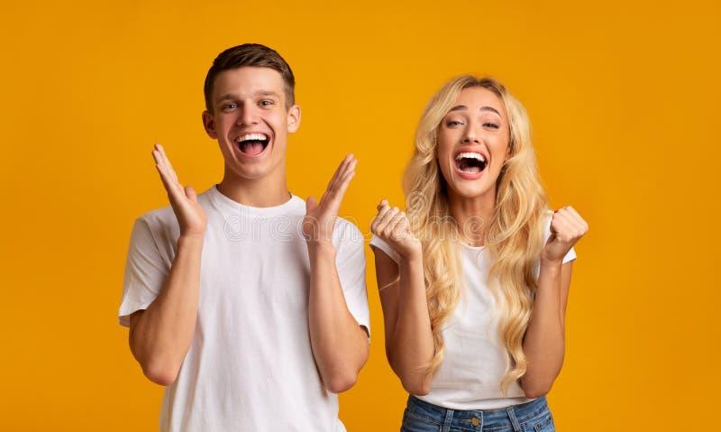 Aufgeregte junge Leute freuen sich über Erfolg, glücklich schreien bei der Kamera lizenzfreie stockbilder