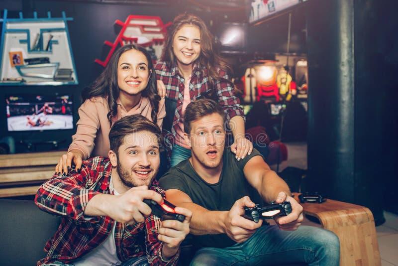 Aufgeregte junge Männer sitzen auf Sofa, wenn sie Raum spielen Sie halten Steuerknüppel und Spielspiel Junge Frauen sitzen hinten stockbild