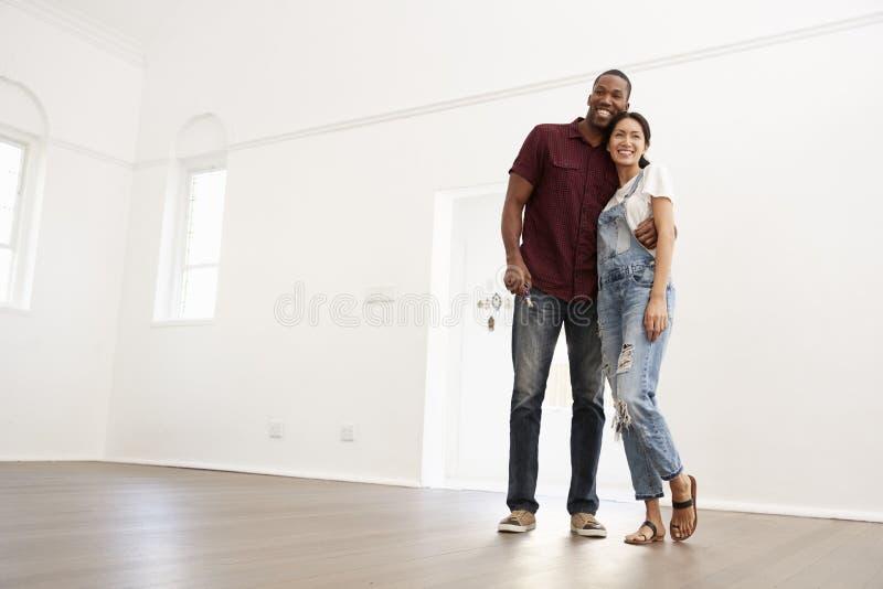 Aufgeregte junge Paare, die in neues Haus zusammenrücken stockfoto
