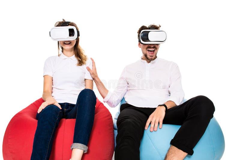Aufgeregte junge Paare, welche die virtuelle Realität gesetzt auf den Sitzsäcken lokalisiert auf weißem Hintergrund erfahren stockfotografie