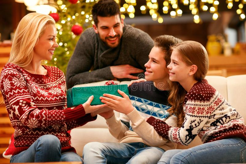 Aufgeregte Kinder, die ihr liebevolles Mutter Weihnachtsgeschenk geben lizenzfreie stockfotografie