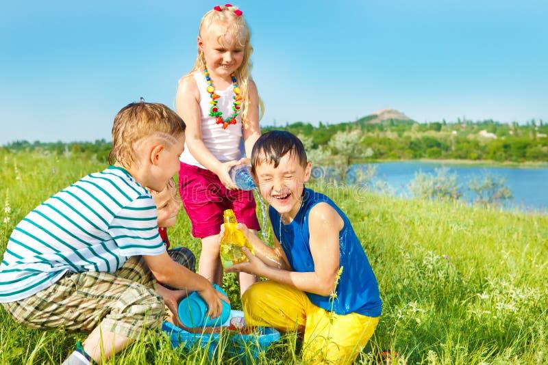Aufgeregte Kinder, die Wasser gießen stockbilder