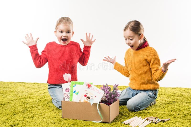 aufgeregte kleine Schwestern mit Kasten Materialien für die Kunst, die auf Boden sitzt lizenzfreie stockfotografie