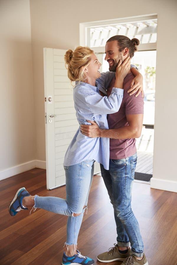 Aufgeregte Paare, die durch offenes neues Haus Front Door In Lounge Ofs umarmen lizenzfreie stockfotos