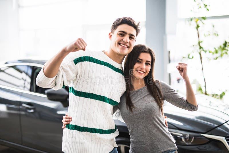 Aufgeregte Paare, die ein Auto am Händler mit Waffen oben kaufen stockbild