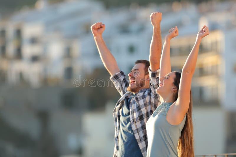 Aufgeregte Paare, die Ferien in einer Stadt feiern lizenzfreie stockfotografie