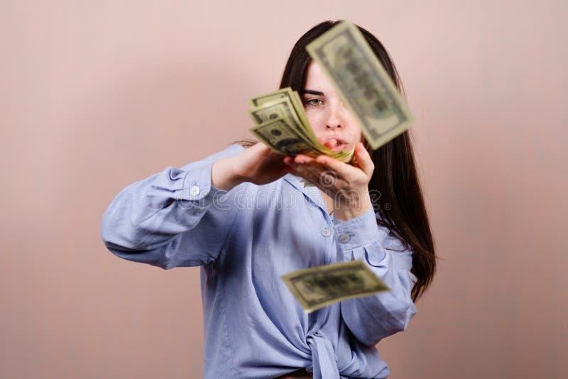 Aufgeregte reiche junge Frau, die Geld zerstreut lizenzfreies stockbild