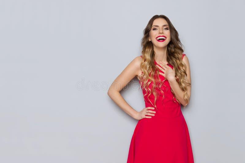 Aufgeregte Schönheit im roten Kleid hält Hand auf Kasten und dem Lachen lizenzfreies stockbild