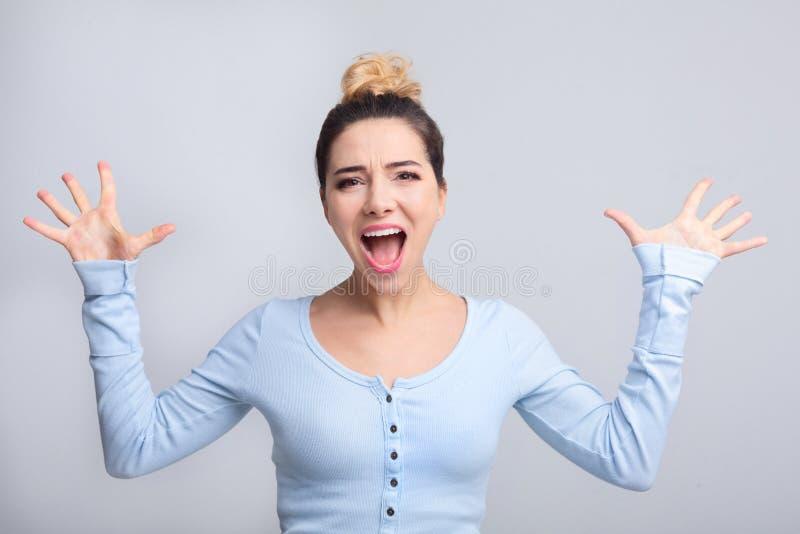 Aufgeregte schreiende junge Frau, die auf Kamera schaut lizenzfreie stockbilder