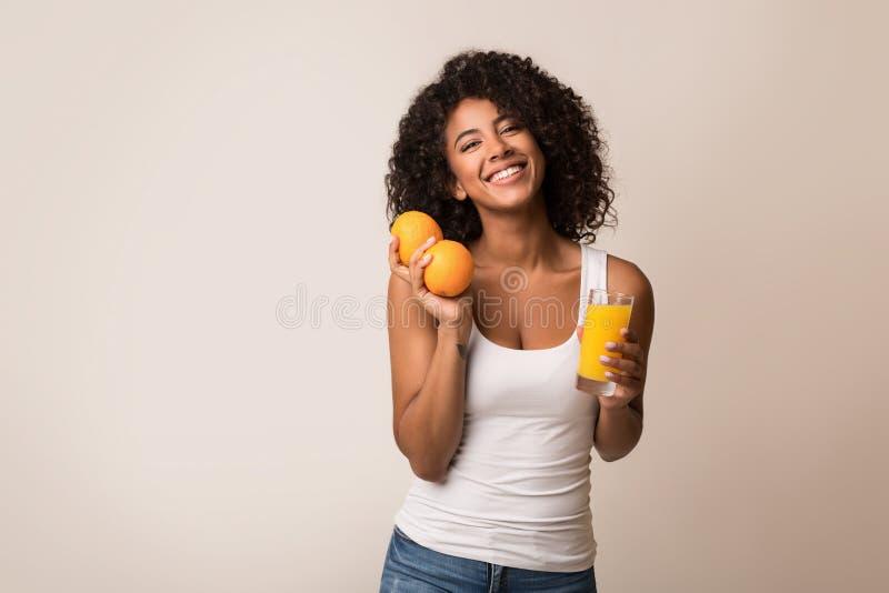 Aufgeregte schwarze Frau mit Orangen und Saft lizenzfreies stockfoto