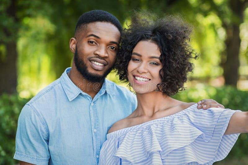 Aufgeregte schwarze Paare, die selfie am Park nehmen stockfotos