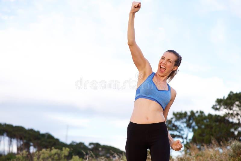 Aufgeregte Sportfrau, die mit den Armen angehoben zujubelt lizenzfreies stockfoto