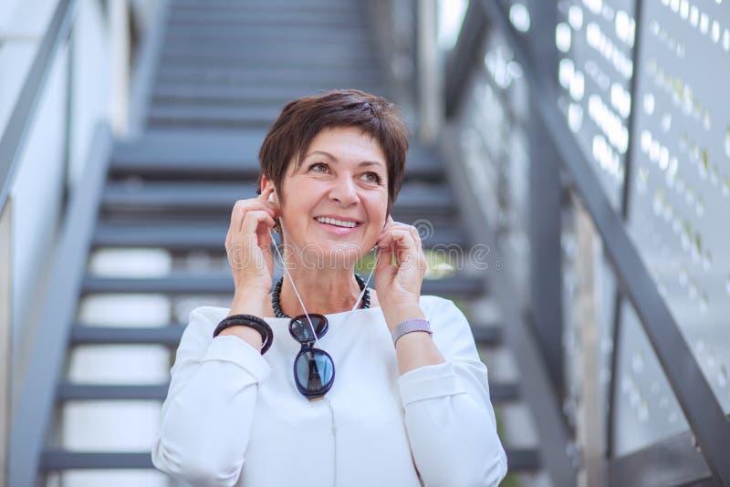 Aufgeregte stilvolle reife Frau in den Kopfhörern hörend Musik auf Straße weg lächelnd lizenzfreie stockfotos
