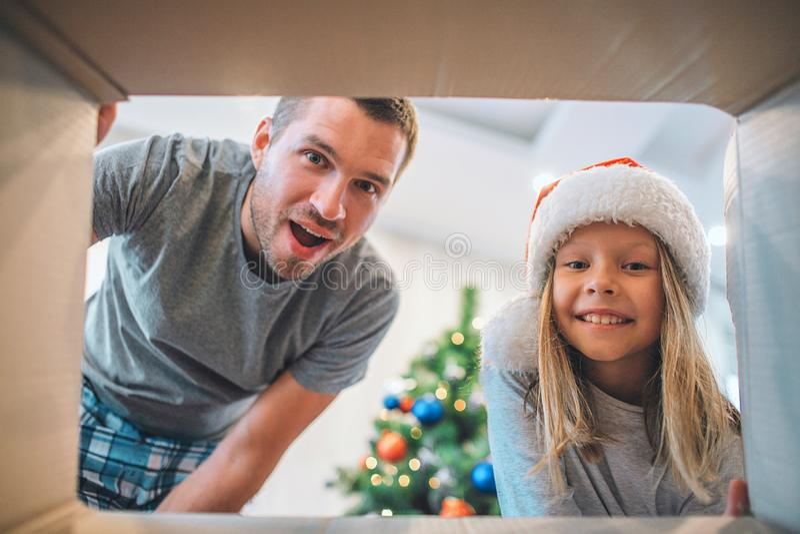 Aufgeregte und glückliche Familie, die nach innen vom Kasten schaut Junger Mann wonderes Mädchen lächelt Sie trägt Hut Es gibt We stockfoto