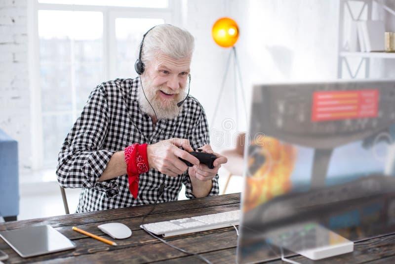 Aufgeregter älterer Mann, der Online-Spiel mit Prüfer spielt stockfoto