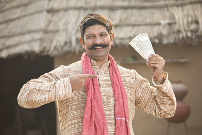 Aufgeregter Anmerkungen haltener und schreiender Landwirt der indischen Rupie stockfoto