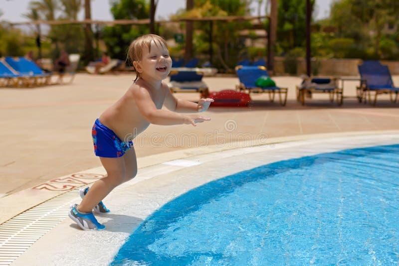Aufgeregter blond-haariger Kinderjunge, der geht, in den Swimmingpool zu springen stockbild