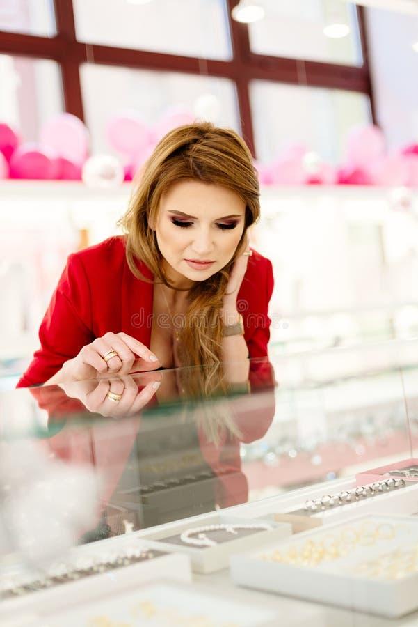 Aufgeregter eleganter kaufender Schmuck der jungen Frau im Juweliergeschäft lizenzfreie stockbilder