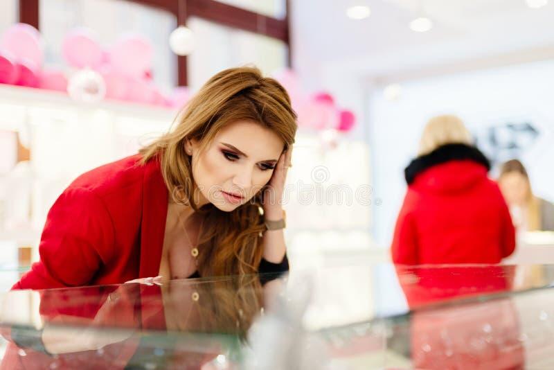 Aufgeregter eleganter kaufender Schmuck der jungen Frau im Juweliergeschäft stockfotos