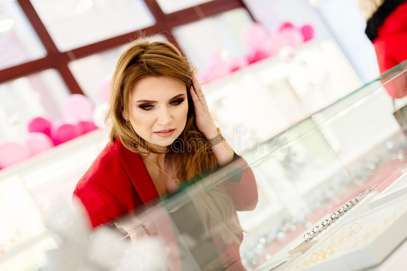 Aufgeregter eleganter kaufender Schmuck der jungen Frau im Juweliergeschäft lizenzfreie stockfotografie