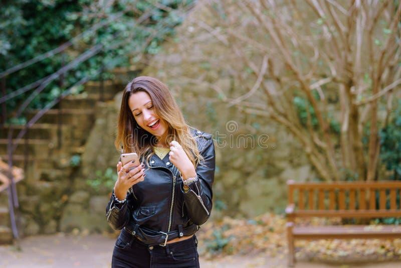 Aufgeregter Frauengrasen Smartphone im Park lizenzfreies stockbild