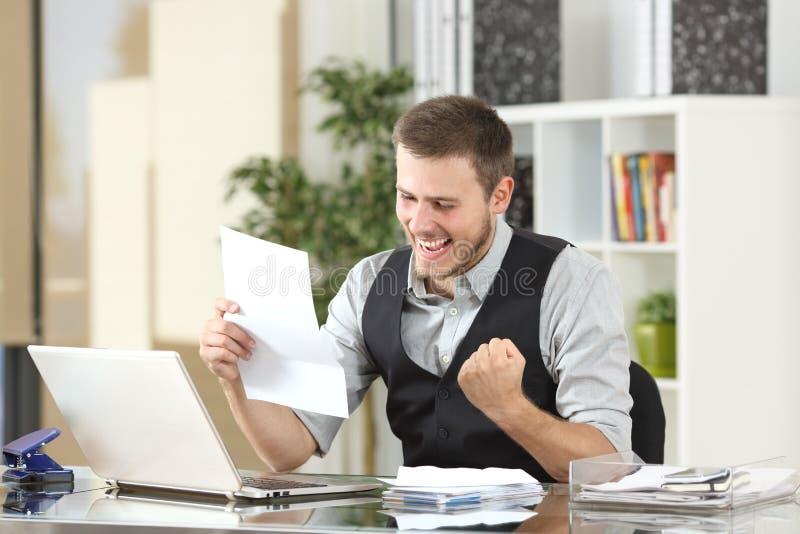 Aufgeregter Geschäftsmann, der einen Brief im Büro liest lizenzfreie stockfotografie