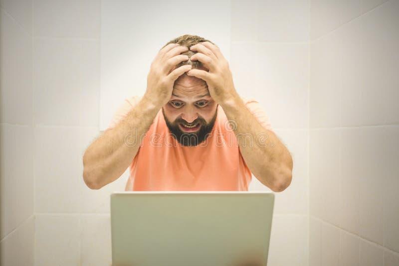 Aufgeregter Geschäftsmann, der an Laptop arbeitet und am Telefon gesetzt auf der Toilette spricht stockfoto
