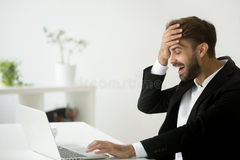 Aufgeregter Geschäftsmann, der wegen Firmengeschäft breakthr lächelt stockfoto
