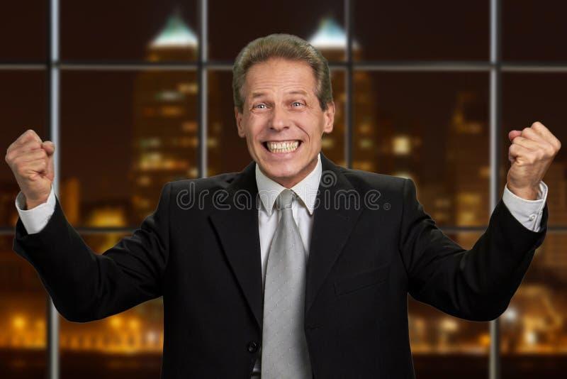 Aufgeregter Geschäftsmann preßte seine Fäuste zusammen stockfoto