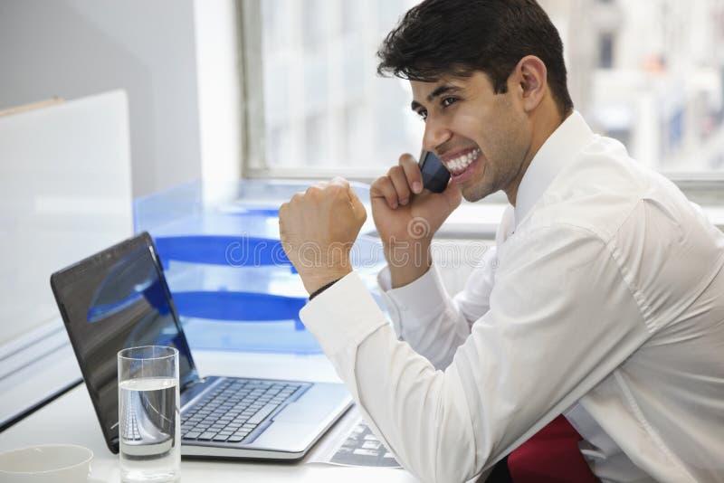 Aufgeregter Geschäftsmann unter Verwendung des Handys am Schreibtisch lizenzfreies stockbild