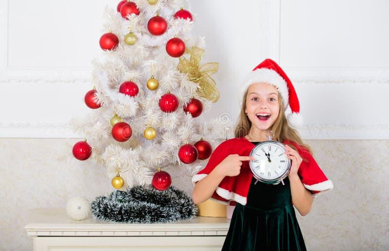 Aufgeregter glücklicher Gesichtsausdruck der Mädchenkinder-Sankt-Hutkostümgriffuhr, der Zeit zum neuen Jahr zählt Letzt bis Mitte stockfotografie