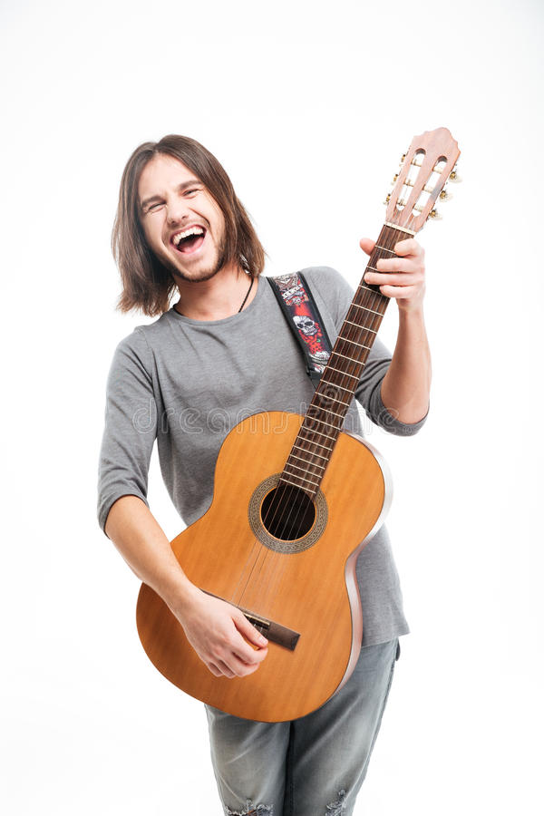 Aufgeregter hübscher junger Mann mit dem langen Haar, das Akustikgitarre spielt lizenzfreies stockbild
