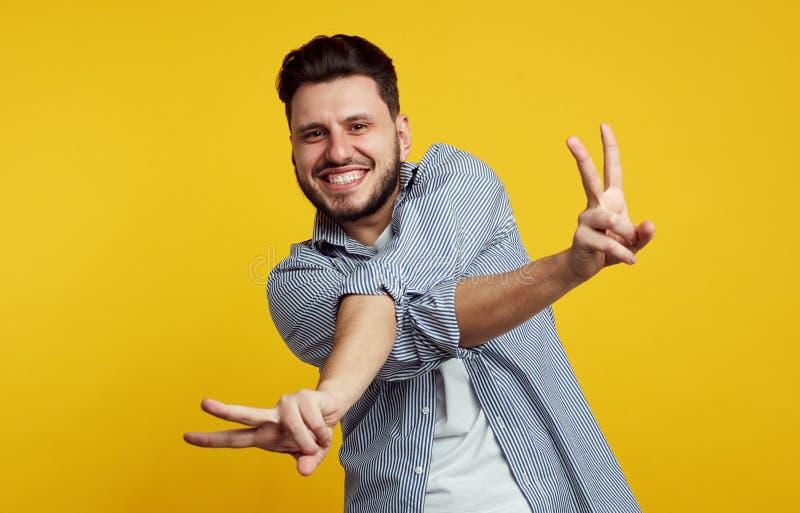 Aufgeregter hübscher Mann gekleidet im stilvollen Hemd und im Zeigen von Friedensgeste mit den gekreuzten Händen lokalisiert über lizenzfreie stockfotografie