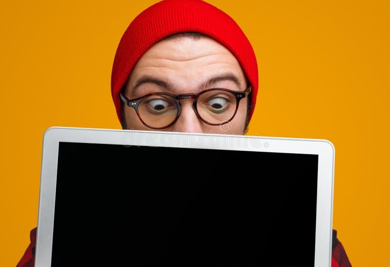 Aufgeregter Hippie, der mit Laptop überrascht schaut lizenzfreie stockfotos