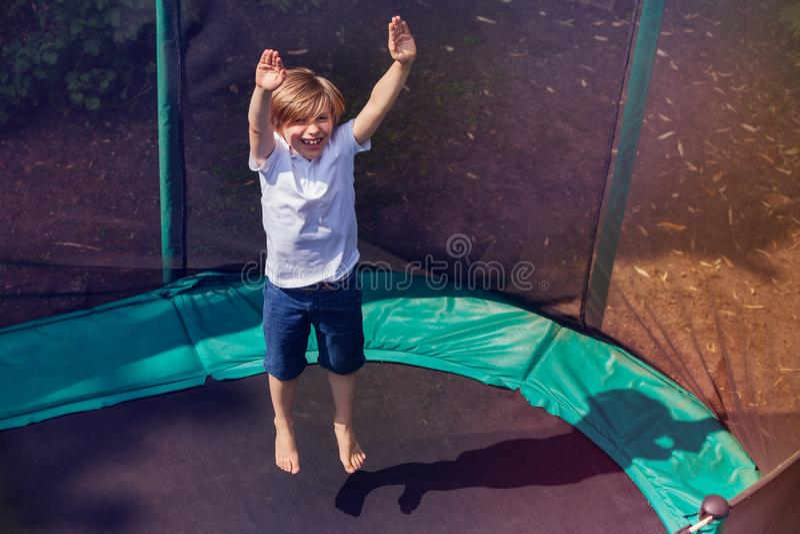 Aufgeregter Junge, der draußen auf die Trampoline aufprallt lizenzfreie stockfotos