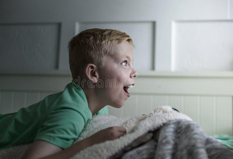 Aufgeregter Junge, der früh im Bett morgens aufwacht Seitenansicht des Jungen untersuchend das Licht oder Licht, die von einem Fe lizenzfreies stockbild