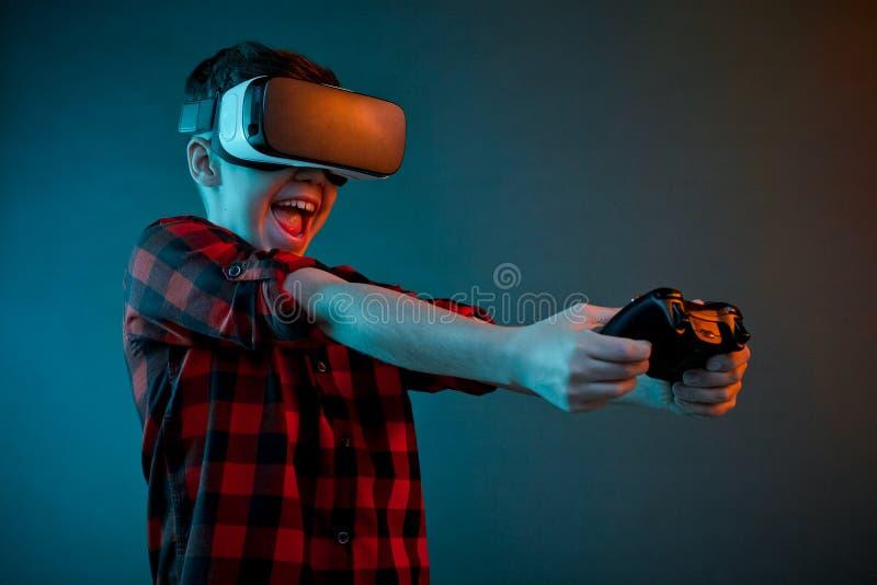 Aufgeregter Junge, der gamepad in VR-Gläsern spielt stockfotografie