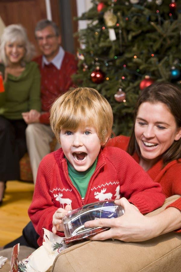 Aufgeregter Junge mit Familie und Geschenke am Weihnachten stockbild