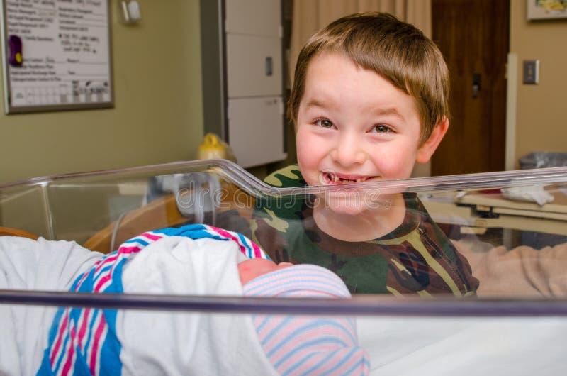 Aufgeregter Junge trifft seine Säuglingsgeschwister nach Lieferung stockfotos