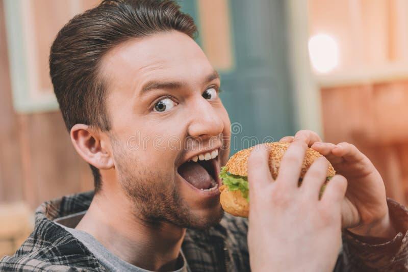 Aufgeregter junger Fleisch fressender frischer geschmackvoller Hamburger und Schauen stockbild